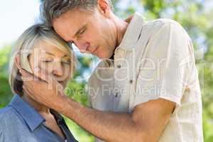 Man comforting woman in park