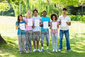 Multiethnic friends holding blank papers