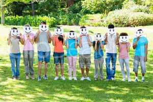Multiethnic friends holding smileys in park