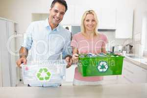 Smiling couple carrying recycling containers in kitchen