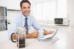 Smiling well dressed man with coffee cup and newspaper in kitche