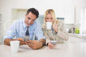 Well dressed couple with coffee cups text messaging in the kitch