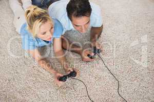 Couple playing video games on area rug at home