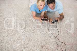 Couple playing video games on area rug