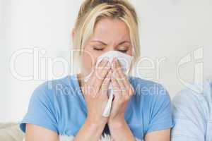 Closeup of a young woman suffering from cold