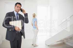 Real estate agent on call with blurred woman in background
