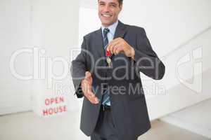 Businessman offering a handshake while holding up keys