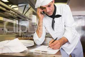Cook writing on clipboard while using cellphone in kitchen