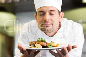 Closeup of a chef with eyes closed smelling food