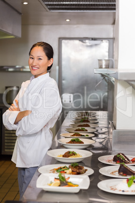 Confident female chef besides cooked food in row at kitchen