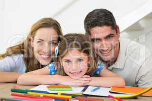Family with book and crayons sitting at table