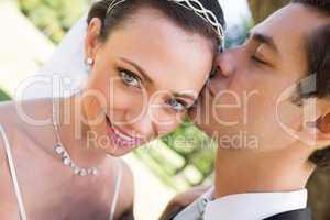 Bride being kissed by groom in garden