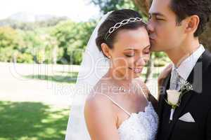 Groom kissing shy bride on head in garden