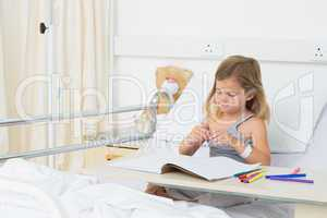 Girl coloring picture book in hospital