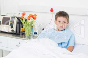 Boy reclining in hospital bed