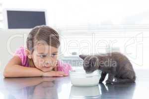 Girl looking at kitten drinking milk from bowl