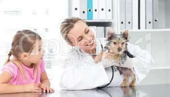 Veterinarian examining puppy with girl