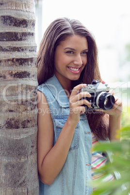 Stylish young girl taking photographs outside