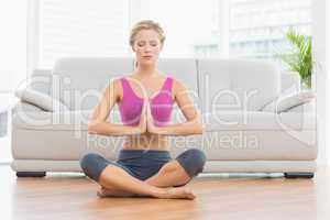 Calm blonde sitting in lotus pose with hands together