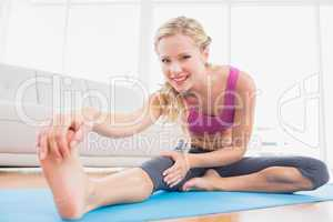 Toned blonde stretching on exercise mat smiling at camera