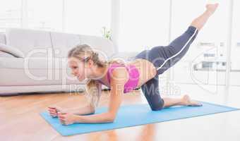 Toned blonde doing pilates on exercise mat