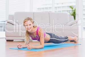 Fit blonde in plank position on exercise mat smiling at camera