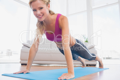 Strong blonde in plank position on exercise mat smiling at camer