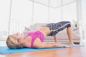 Slim blonde doing pilates on exercise mat