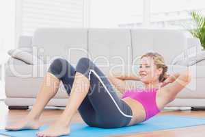 Slim blonde doing sit ups on exercise mat