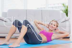 Slim blonde doing sit ups on exercise mat smiling at camera