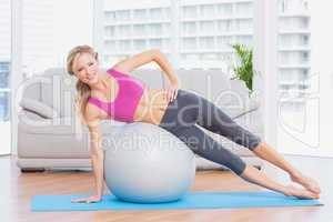 Cheerful fit blonde doing side plank with exercise ball