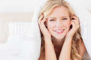 Cute blonde smiling at camera from under the duvet