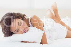 Sleeping brunette lying on bed holding pillow