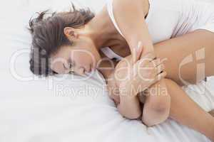 Unhappy brunette lying on bed holding her knees