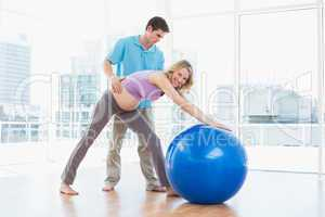 Trainer exercising with smiling pregnant client and exercise bal