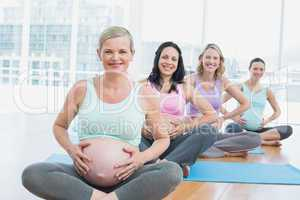 Pregnant women in yoga class sitting on mats touching their bump