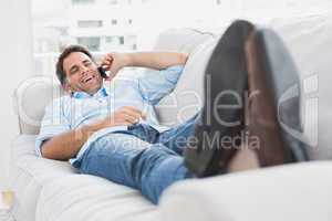 Happy man lying on the couch chatting on the phone