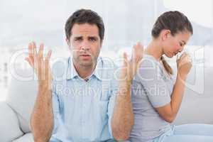 Man gesturing at camera with his crying partner on the couch
