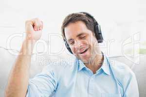 Singing man sitting on sofa listening to music with eyes closed