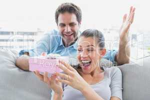 Man surprising his pretty girlfriend with a pink gift on the sof