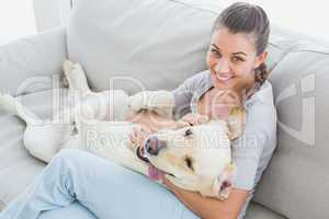 Happy woman rubbing her yellow labrador on the couch