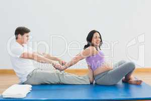 Masseur stretching pregnant womans arms and shoulders