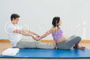Masseur stretching pregnant womans arms and shoulders on a mat