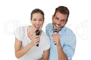 Portrait of a cheerful couple singing into microphones