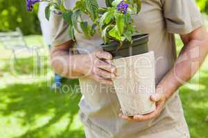 Mid section of a man holding flower pot at park