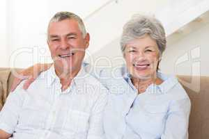 Retired couple sitting on couch smiling at camera