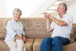 Retired man taking photo of his partner on the couch