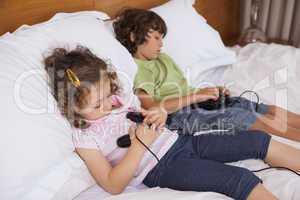 Asleep siblings while playing video games in bedroom