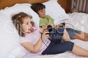 Brother and sister playing video games in bedroom