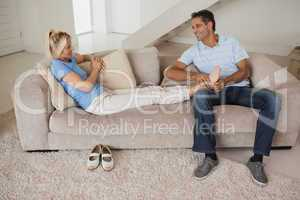 Full length of a relaxed couple sitting in living room